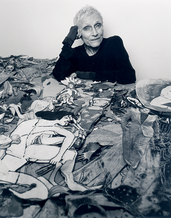 "Portrait of the artist with her mounds of ""paper dolls."""