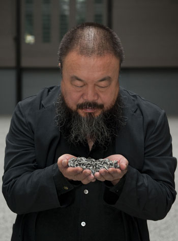 Ai Weiwei with porcelain seeds from his installation Sunflower Seeds, 2010, which filled the Turbine Hall at London's Tate Modern with 100 million of the replicas.