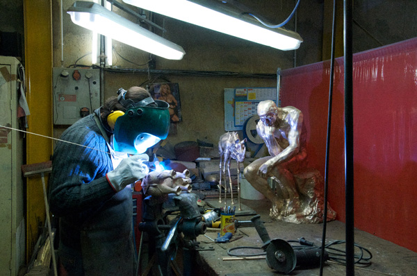 An artisan at the Valsuani Foundry working on a  Dalí sculpture. On the table, Rodin's The Thinker and another work  by Dalí.