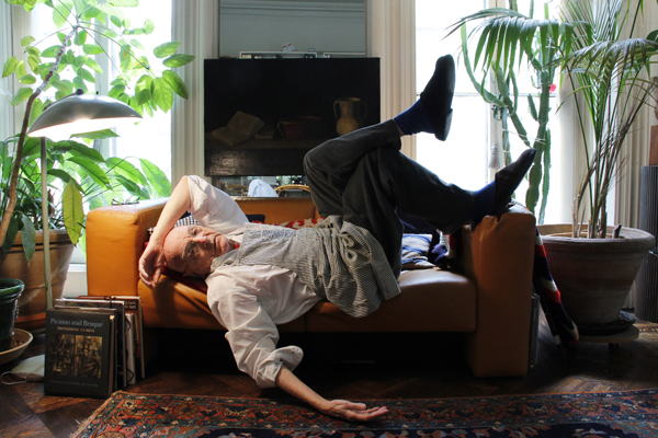 Duane Michals strikes a pose on the couch of his New York apartment. ©2013 REBECCA ROBERTSON