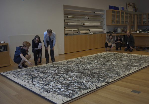 Curators and conservators gather to examine  One: Number 31, 1950. IMAGE COURTESY MOMA.