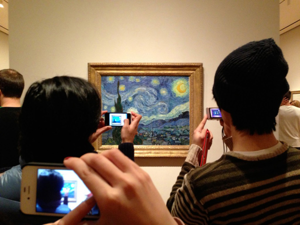 Museumgoers snapping photos of Vincent van Gogh's Starry Night, 1889, at MoMA. ©2013 REBECCA ROBERTSON.