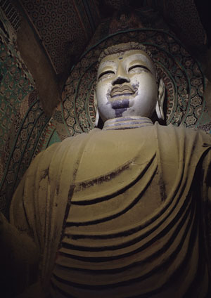 The colossal figure of a seated Buddha in Cave 130, Tang dynasty (eighth century), is more than 85 feet high. COURTESY DUNHUANG ACADEMY
