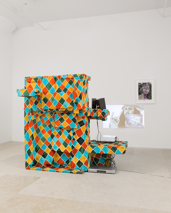 Rachel Harrison, Sops for Cerberus, 2008, wood, polystyrene, cement, acrylic, fake carrots, projector, speakers, DVD player, framed mixed media on ink-jet print, and Vanity Fare video, 6 minutes (2007).COURTESY THE ARTIST AND GREENE NAFTALI, NEW YORK. PHOTO: JASON MANDELLA.