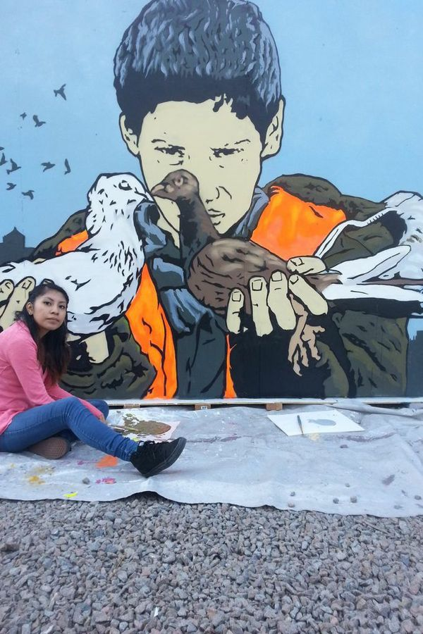 Apprentice Cynthia Martinez poses with Chris Stain's image of a boy with two pigeons.