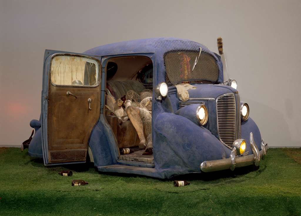 Edward Kienholz, Back Seat Dodge '38, 1964, paint, fiberglass and flock, 1938 Dodge, recorded music and player, chicken wire, beer bottles, artificial grass, and cast plaster figures, 66 x 120 x 156 inches. MUSEUM ASSOCIATES, LACMA/©ED KIENHOLZ/LOS ANGELES COUNTY MUSEUM OF ART