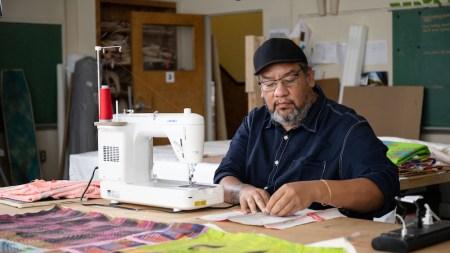 Jeffrey Gibson sewing in his studio.
