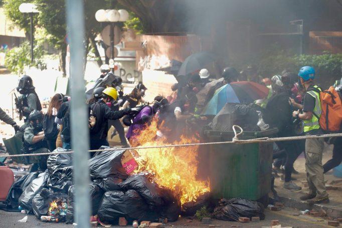 Protesters run past burning debris as