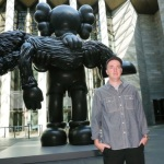 KAWS with his sculpture 'GONE' at