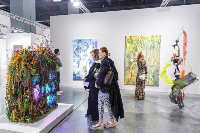 Visitors examine a work by Max