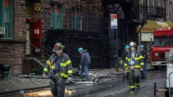 Firefighters leave a building that house several nonprofits and a senior center, which was destroyed by fire overnight in Chinatown, in New York