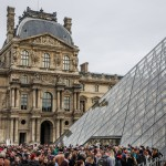 Visitors queue outside the Louvre.