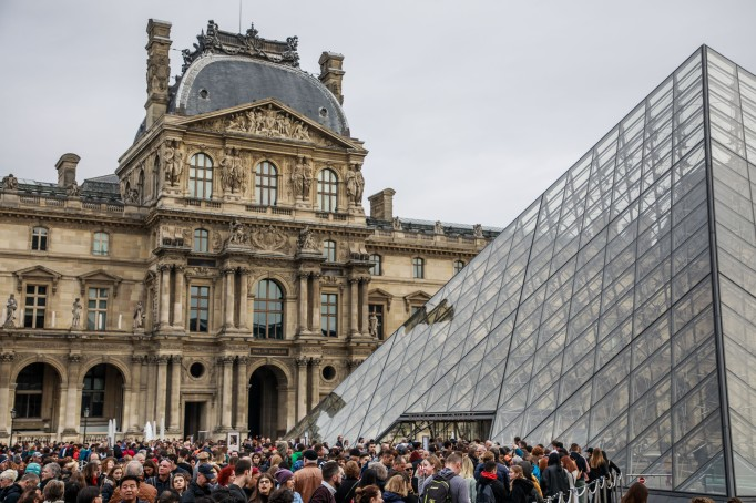 Visitors queue outside the Louvre.