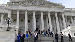 Members of the House of Representatives walk down the steps of Capitol Hill after passing a coronavirus rescue package.