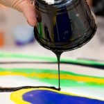 A person pours a small stream of black paint from a plastic cup onto a canvas with swirls of green neon and yellow during the process of fluid painting with acrylic paints mixed with floetrol medium.