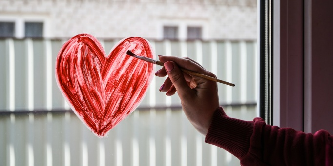 painting red heart on a window