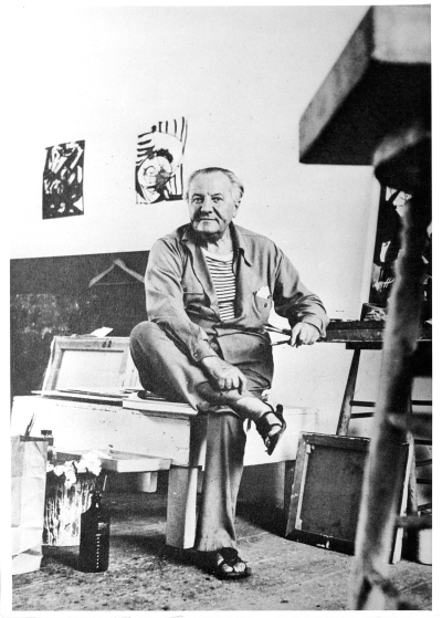 black and white photo of Hans Hofmann sitting in his studio with some artworks in the background