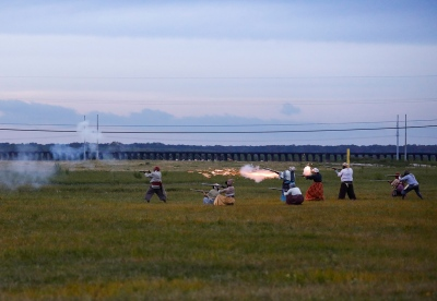 a grassy field with several people in the distance shooting guns