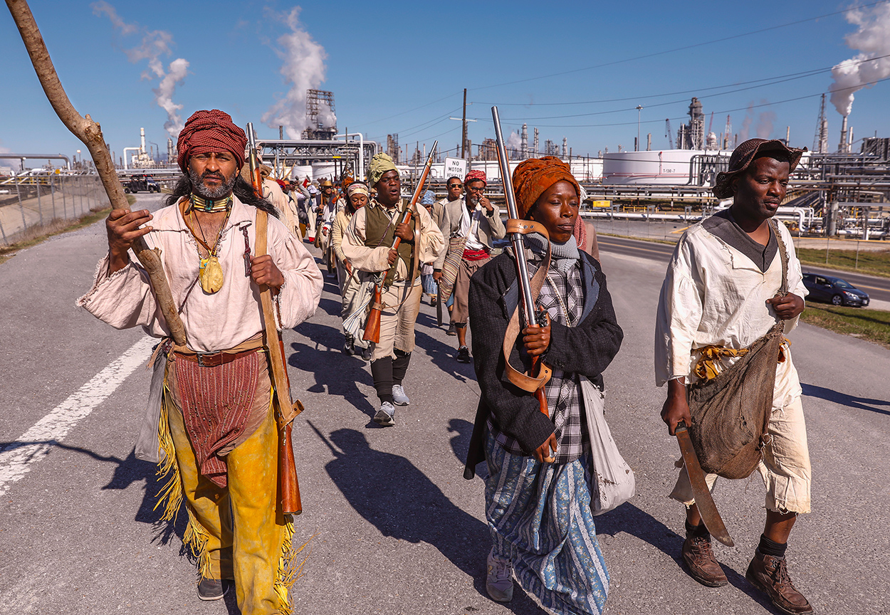A group of people led by two men and a woman, holding guns and knives, walking down a road with a power plant in the background