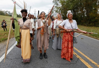a group of people led by three black women in early 19th century dress walking along a road, two holding guns and one holding a green flag