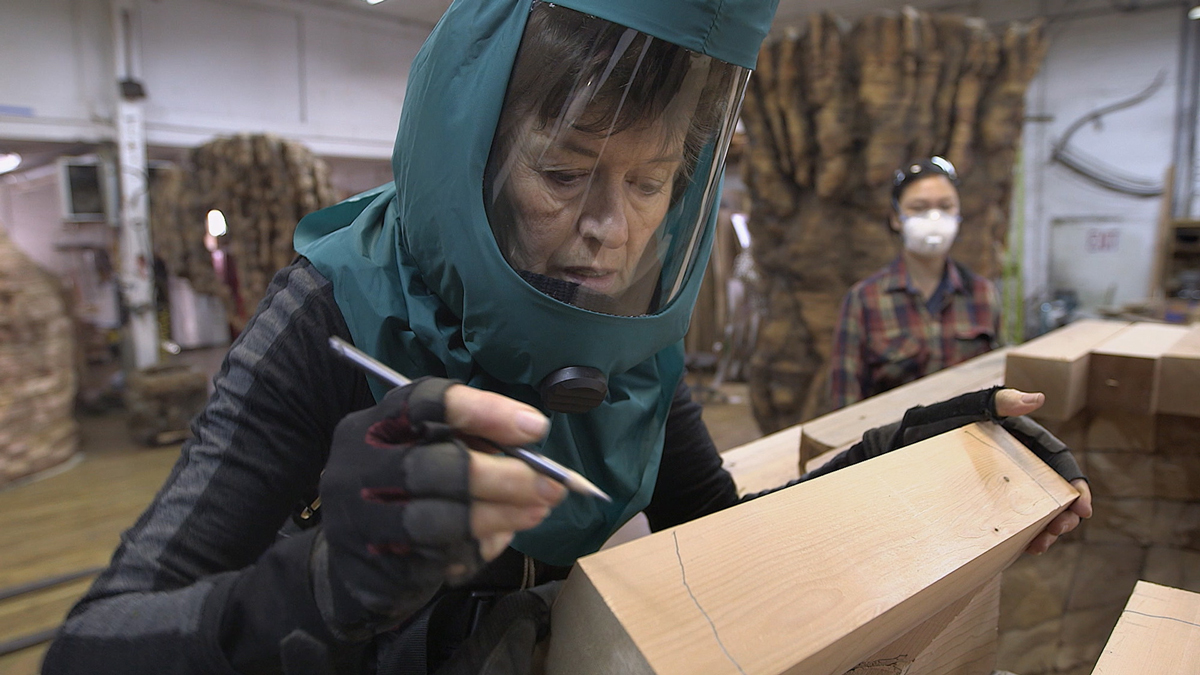 Ursula von Rydingsvard drawing cut lines on 4x4 cedar beams, which will later be cut with a chainsaw by her assistants, 2015.