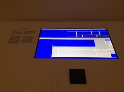 An abstract composition comprising html frames on a website is shown on a screen in a museum vitrine