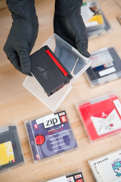 Gloved hands hold a black cartridge for data storage and its transparent plastic case