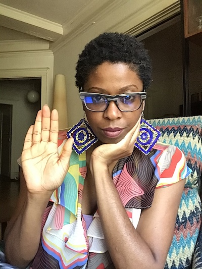 Stacy Patrice raising her hand to the camera and wearing a patterned shirt.