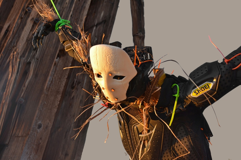 A strawman wearing a white mask and black body armor is suspended from sunbleached wooden beams by bright orange and green zip ties