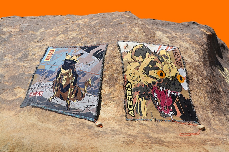 Two tapestries showing hyenas are displayed on a bare rocky surface against a bright orange backdrop.