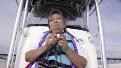 an older woman in a blue and purple life vest sit on a boat, holding a tiny cup