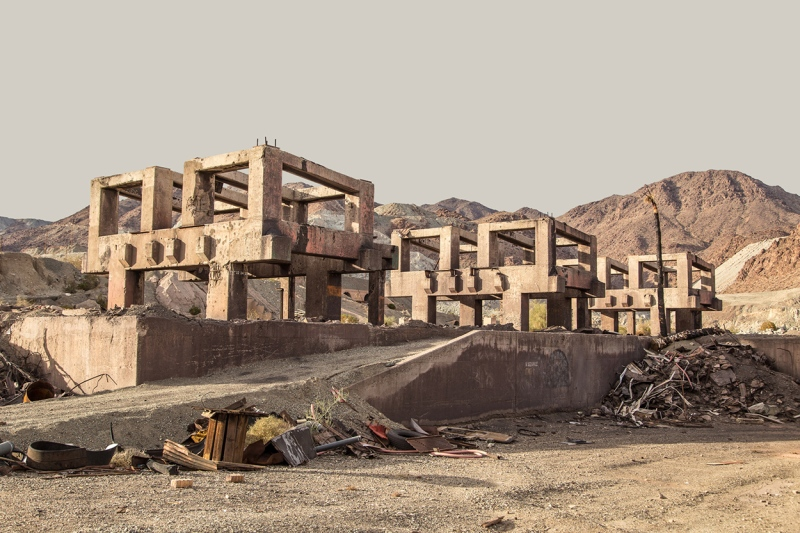 Boxy concrete ruins in a washed-out desert landscape