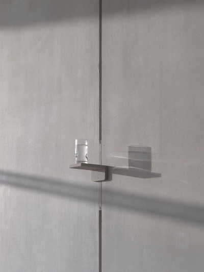 gray cement wall with a partially full water glass on a small shelf