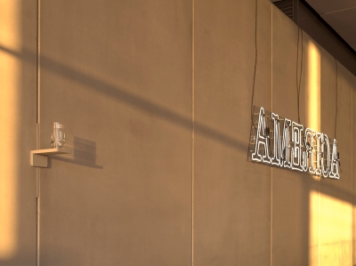 "view of a cement wall with a partially full water glass on a little shelf on the left and a neon sign spelling ""America"" in white block letters on the right"