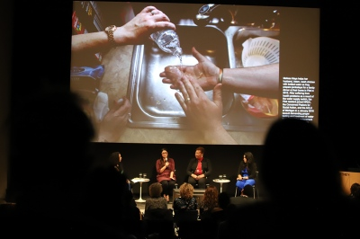 dark auditorium showing four women on stage and a screen with a close-up on someone pouring bottled water onto their hands in a metal kitchen sink