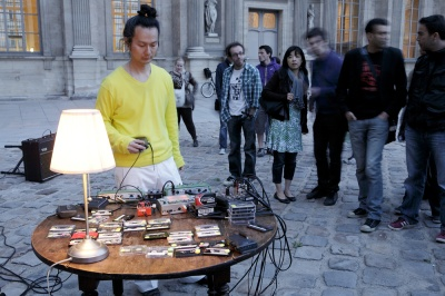 Aki Onda performing outside the Louvre with a table of cassette tapes and walkmen.