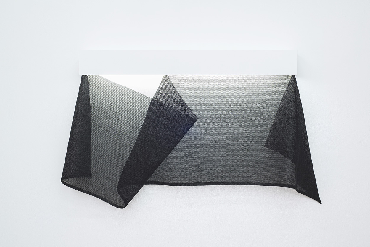 wall sculpture made of a piece of folded and draped black screen