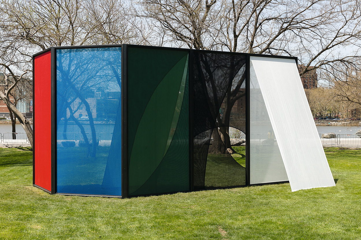 3D structure made of black, white, red, and blue screens installed outdoors