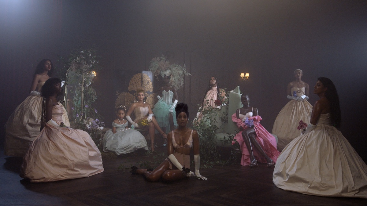 Beyoncé, Blue Ivy Carter and Kelly Rowland in 'Black Is King' wearing gowns and posed in a darkened room.