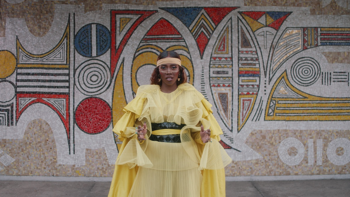 Tiwa Savage in 'BLACK IS KING' wearing a yellow gown and set against an abstract wall painting.