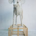 A styrofoam sculpture of a calf stands atop a wooden armature.