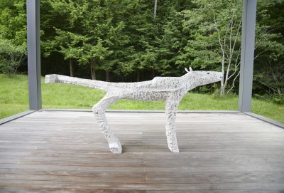 A white sculpture of a large, slender fox with a crumply surface. It's place outdoors, on a wooden platform and among green trees.