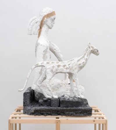 A styrofoam sculpture of a girl kneeling next to a slender cat atop of a wooden armature.