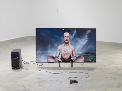 A digital avatar of a bald man with faces tattooed on his bare torso appears on a monitor installed on a gallery floor