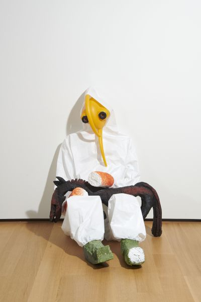 A figurative sculpture in a hazmat suit with a yellow watering can for a face. They are holding a small mammal that appears covered in oil.