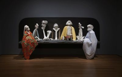 6 humans and 1 dog, all sculpted in Styrofoam, sit atop a dark styrofoam plinth.