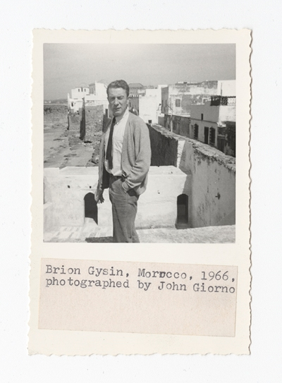 An image from a scrapbook with black-and-white photo of a man in a suit, squinting in the sunlight reflecting off white-walled Moroccan buildings