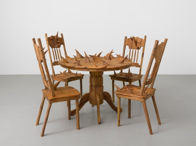 wooden table and four chairs covered with carved thorns