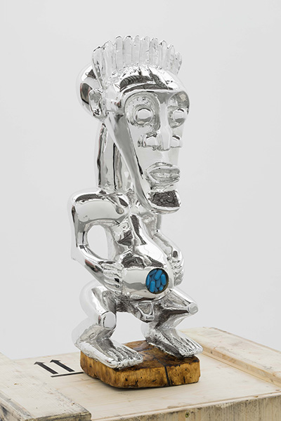 silver plated African figurine on a wooden crate with blue pills embedded in its belly