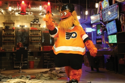 The hairy orange hockey mascot stands in a cinderblock-walled basement, with s